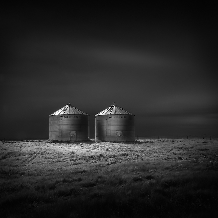Grain bins overlooking an empty pasture