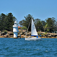 Shark Island Light in Sydney, Australia<br /> Shark Island is a tiny, 3.7 acre rocky islet near Rose Bay in Sydney Harbour. It is only accessible by water like this passing sailboat or by ferry. Protecting the shoreline is a pile light. This 39 foot tall, cylindrical tower was built in 1913 and remains operational.