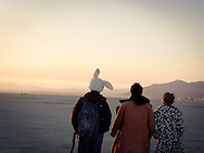 3 burners walk into the desert at sunrise, one wearing curious fuzzy bunny hat, Burning Man