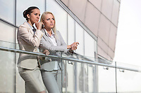 Young businesswomen on office railing looking away