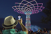 A visitor of Expo 2015 films with her smartphone the spectacle of the Tree of Life at the Lake Arena, Rho-Pero, Milan, in June 2015. &copy; Carlo Cerchioli<br /> <br /> Una visitatrice di Expo 2015 riprende con il suo smartphone lo spettacolo dell'Albero della vita alla Lake Arena, Rho-Pero, Milano, giugno 2015.