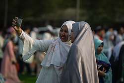February 14, 2013 - Central Jakarta, Jakarta, Indonesia - Womans take selfie after Eid Al-Fitr prayer on plastic grass at futsal stadium on June 15, 2018 in Jakarta, Indonesia. Muslims around the world are celebrating Eid al-Fitr, the three day festival marking the end of the Muslim holy month of Ramadan, it will be observed on 15th or 16th of June depending on the lunar calendar. Eid al-Fitr is one of the two major holidays in Islam. (Credit Image: © Afriadi Hikmal via ZUMA Wire)