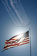Planes fly in formation past the American flag during the national anthem before a NASCAR Sprint Cup Series auto race at Kansas Speedway in Kansas City, Kan., Sunday, Oct. 5, 2014. (AP Photo/Colin E. Braley)