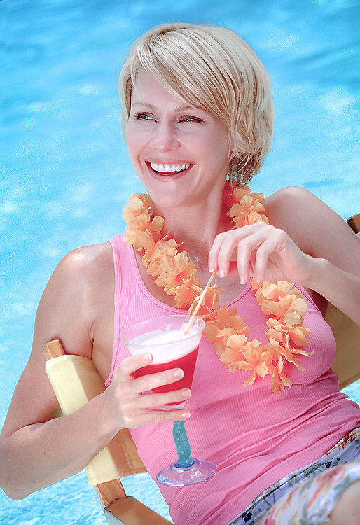 Smiling wmna, 30-35, holding tropical drink with unbrella garnish, pool background.