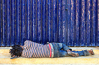 Home Street Home: A homeless man finds a moment's sleep, using his flip flops as a pillow, on the stairs of a locked doorway, Wat Ounalom, Phnom Penh Cambodia.