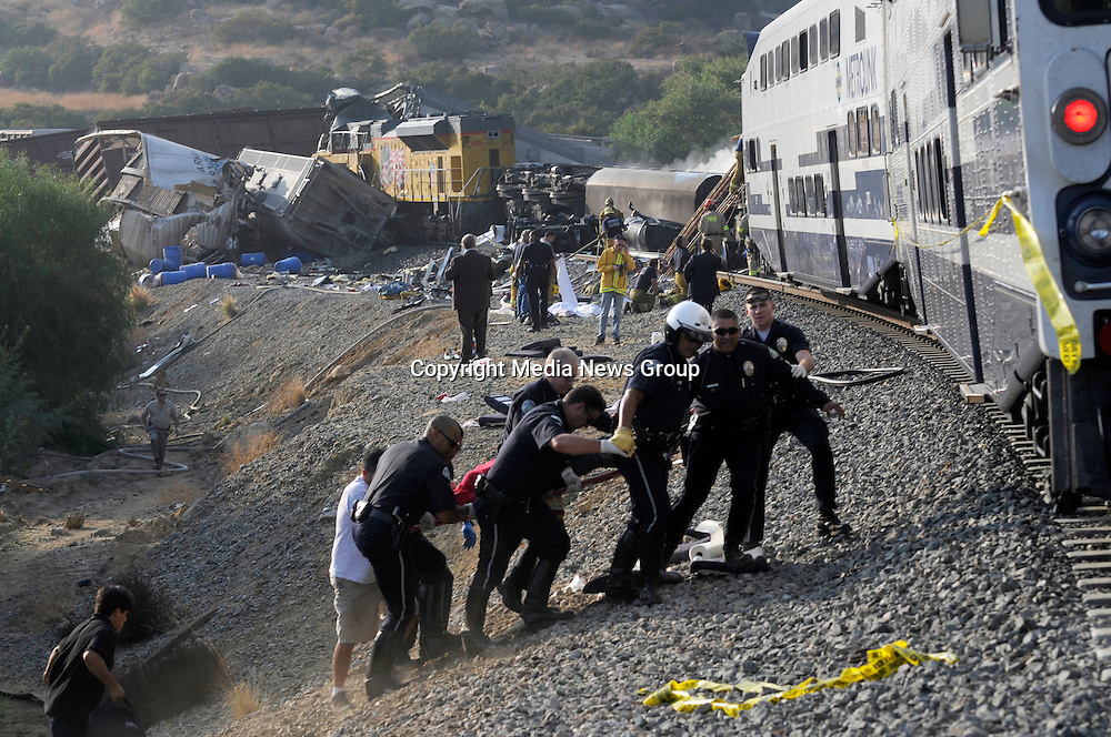 Rescue workers work to remove victims who were traped inside the wreckage of a MetroLink commuter train that collided with a freight train in the Chatsworth CA are of Los Angeles on Friday, Sept. 12, 2008.  Photo by John McCoy/staff photographer.