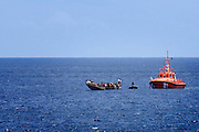 "Tenerife / Los Cristianos June 7, 2006 - A fishing boat called ""Cayucos"" by the inhabitants of the island, with 85 would-be immigrants from West Africa intercepted by Spanish police off the coast of Tenerife in the Canary Islands are seen in an open wooden fishing vessel as they approach the port of Los Cristianos. They arrived on June, carrying 85 would-be immigrants, in the archipelago which has received more than 7,000 Africans so far this year, more than half to the tourist resort island of Tenerife. At least 1,000 more are believed to have died trying to make the sea crossing, mostly in small fishing boats"