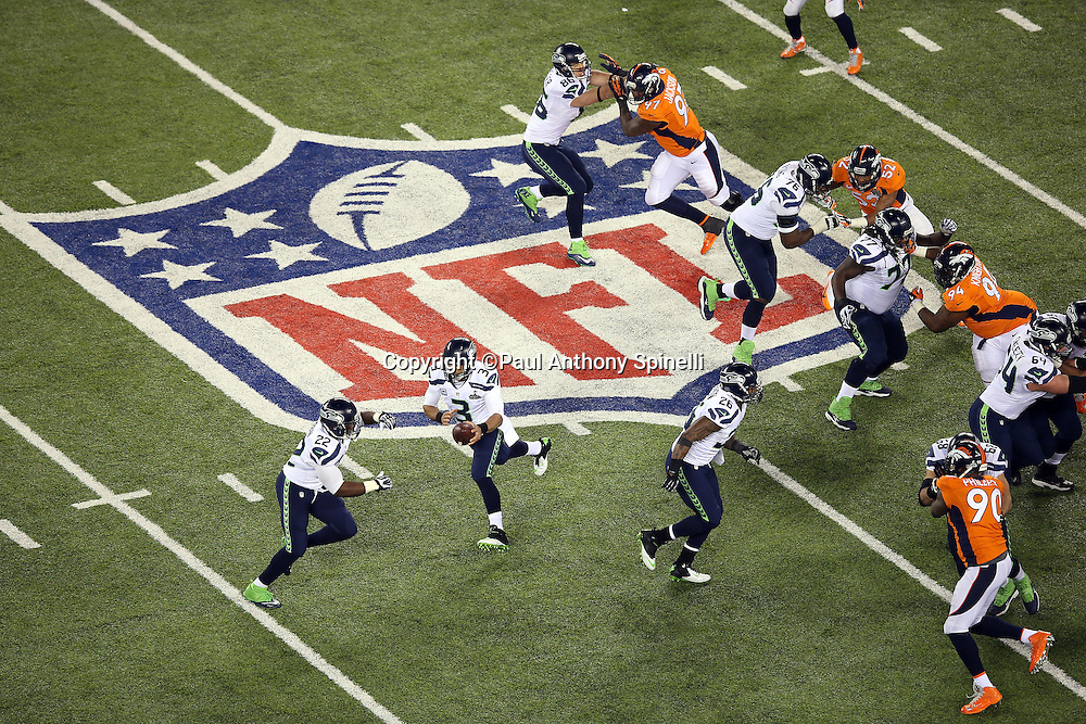 Seattle Seahawks quarterback Russell Wilson (3) hands off the ball to Seattle Seahawks running back Robert Turbin (22) as the teams grapple while standing on the NFL logo painted on the field during the NFL Super Bowl XLVIII football game against the Denver Broncos on Sunday, Feb. 2, 2014 in East Rutherford, N.J. The Seahawks won the game 43-8. ©Paul Anthony Spinelli