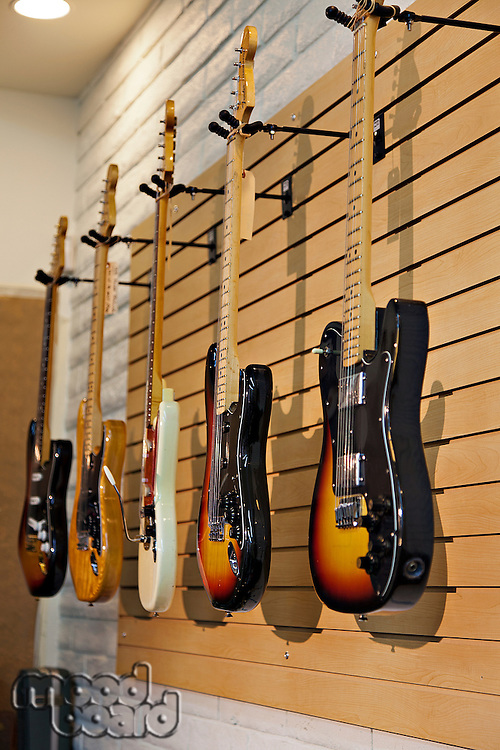 Five electric guitars hanging on display rack in store for sale