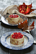 Autumn  risotto, prepared with scamorza cheese and smoked tuna fish, decorated with pomegranate seeds and dry leaves.