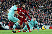 Liverpool striker Mohamed Salah (11) lays the ball off between Arsenal defender Sokratis Papastathopoulos (5) and Arsenal midfielder Aaron Ramsey (8) during the Premier League match between Liverpool and Arsenal at Anfield, Liverpool, England on 29 December 2018.