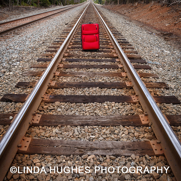 Red suitcase on a railroad track