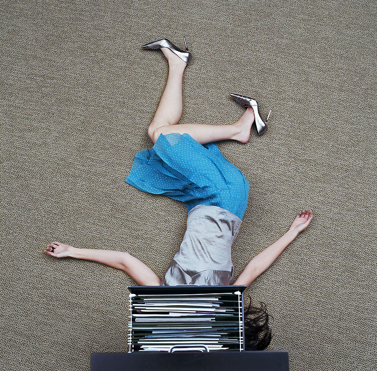 Woman lying on floor under open filing cabinet drawer, overhead view