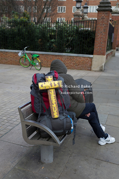 A Christian man sits on a bench outside the Design Museum on Kensington High Street, on 6th January 2019, in London, England.