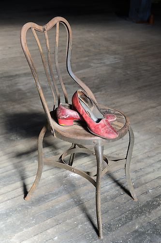 Old And Worn Out Red Shoes On A Rusty Metal Chair With A Dirty Wooden Floor