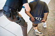 03 APRIL 2008 -- GUADALUPE, AZ:  Undercover deputies with the Maricopa County Sheriff's Department arrest a man wanted on misdemeanor warrants and drug possession during an anti-crime sweep in Guadalupe, AZ, Thursday. The Maricopa County Sheriff's Department has started high profile zero tolerance crime sweeps targeting illegal immigrants but also arresting anyone they find breaking the law or with outstanding warrants. All of the previous sweeps have been in Phoenix city limits. This was the first one outside Phoenix, Guadalupe is a working class unincorporated town south of Phoenix. Most of the town's residents are Native Americans and Hispanics and hundreds of people lined the street to protest the sweep.  In 2011, the US Department of Justice issued a report highly critical of the Maricopa County Sheriff's Department and the jails. The DOJ said the Sheriff's Dept. engages in widespread discrimination against Latinos during traffic stops and immigration enforcement, violates the rights of Spanish speaking prisoners in the jails and retaliates against the Sheriff's political opponents.     PHOTO BY JACK KURTZ
