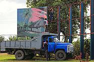 Removing a sign in Las Coloradas, Granma, Cuba.