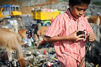 Taupik, 14, sharpening his picking tool at the 'Trash mountain', Makassar, Sulawesi, Indonesia.