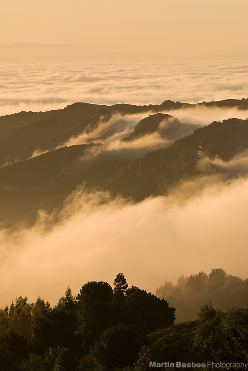 Fog rolls over the Oakland Hills at sunrise, California