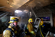 Firefighters battle to contain flames to a home on fire in the Bel Air neighborhood of Los Angeles, Wednesday, Dec. 6, 2017.