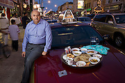 Din Memon, a Chicago taxi driver, with his typical day's worth of food arranged on the hood of his leased cab on Devon Avenue in Chicago, Illinois. (From the book What I Eat: Around the World in 80 Diets.) The caloric value of his day's worth of food in the month of September was 2,000 kcals. He is 59 years of age; 5 feet, 7 inches tall; and 240 pounds. Din came to the United States as a young man in search of freedom and opportunity and remains pleased with what he found. He has lived in Chicago for 25 years and has been driving a cab for the past two decades, five to six days a week, 10 hours a day. He knows where all of the best Indian and Pakistani restaurants are throughout Chicago, but prefers his wife's home cooking above all. His favorites? ?Kebabs, chicken tika, or biryani?spicy food,? he says. Tika is dry-roasted marinated meat, and biryani is a rice dish with meat, fish, or vegetables that is highly seasoned with saffron or turmeric. MODEL RELEASED. .