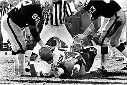 Oakland Raiders Art Thoms, Horace Jones and Ted Hendricks over sacked quarterback Cincinnati Bengal Ken Anderson. (1975 photo/Ron Riesterer)