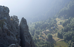 View of hiker seen climbing up over peak of Martinswand mountain, Hohneck, Vosges, France