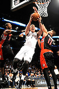 Toronto Raptors' Terrence Ross (31) and Jonas Valanciunas (17) block Brooklyn Nets' Mason Plumlee's (1) shot at the basket during an NBA basketball game on Monday, March 10, 2014 at Barclays Center in New York. (AP Photo/Kathy Kmonicek)