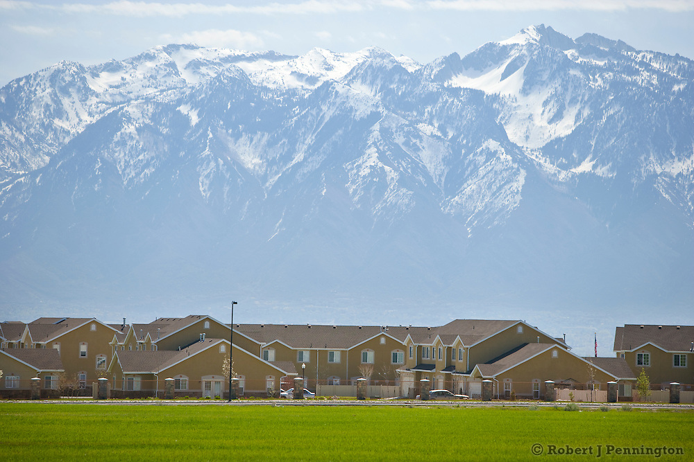 Tightly-packed housing spreads across a landscape of green farming fields with majestic mountains in the distance.