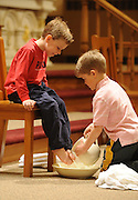 Two boys participate in the washing of feet during a Holy Thursday Mass in Algoma, Wis. (Sam Lucero photo)