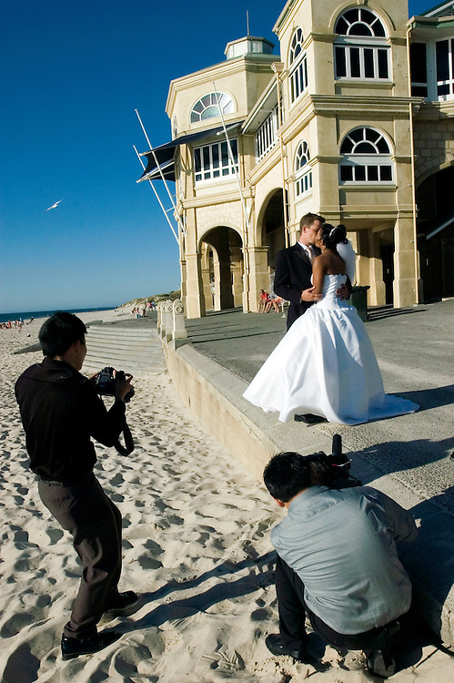 Newly married couple pose for Wedding photographs at Cottesloe Beach, Perth Western Australia 17/12/05.Photograph David Dare Parker for The New York Times