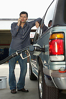 Man using cell phone leaning on van with fuel pump