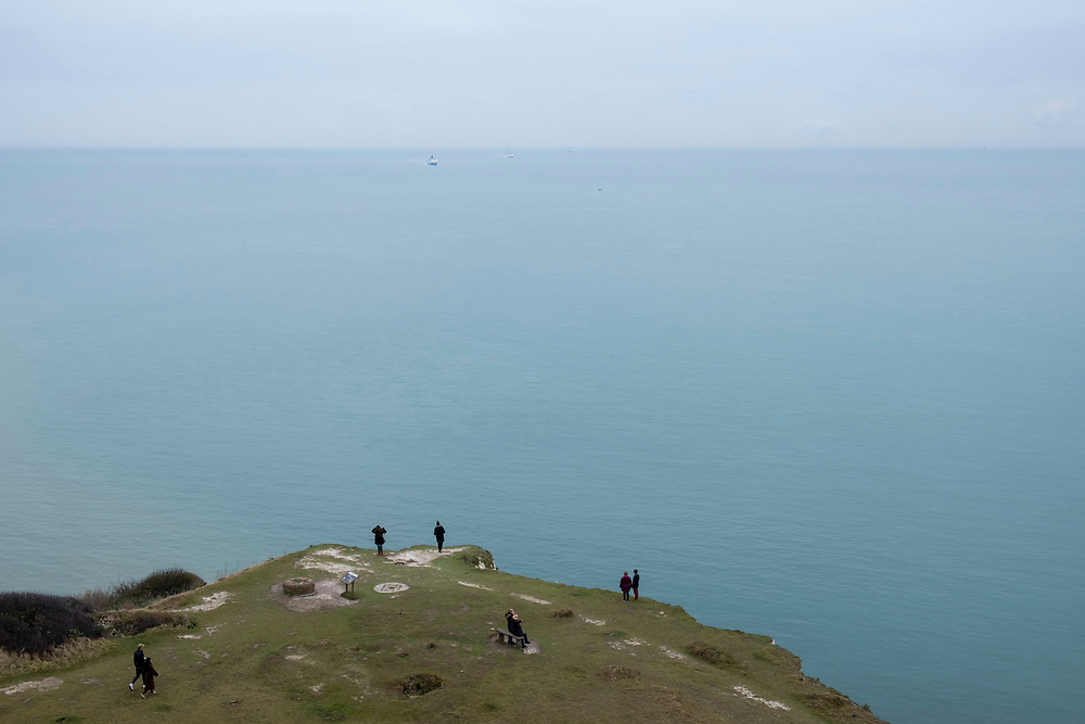 Tourists standing on the edge of the White Cliffs of Dover, Kent. One of the most famous and iconic landmarks of Britain. They face the straights of Dover between England and France. They are part of the North Downs formation and are mostly made up of chalk.  (photo by Andrew Aitchison / In pictures via Getty Images)