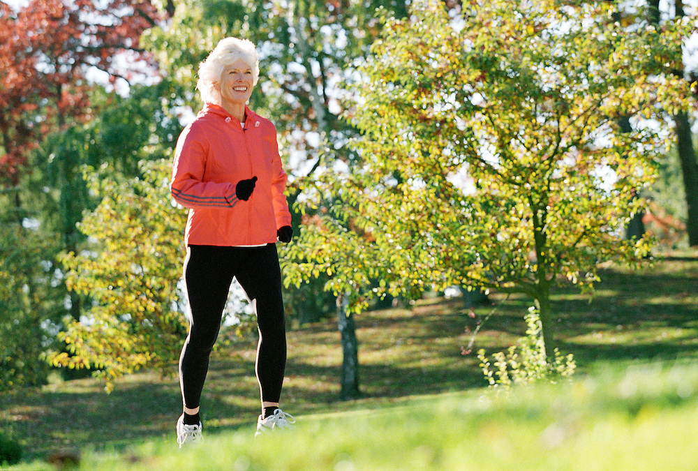A smiling mature woman running ina park on a sunny day.