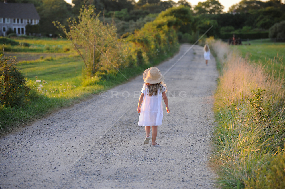 little girl in a pretty dress walking down a dirt road in The Hamptons