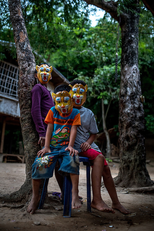 Children wear plastic masks in the village of Khoc Kham. With the introduction of affordable outboard motors, the villagers, who have no road access to the outside world, can trade with nearby villages.
