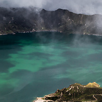 At 3900 meters on the crown of Quilotoa Crater Lake, spots of sunlight shine through the dense cloud and fog billowing over the ridge, creating many textures and colors upon the emerald waters of this Ecuadorian gem. The green hue of the water is due to dislolved minerals. The original image is a double image high resolution panoramic.