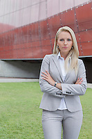 Portrait of confident businesswoman standing with arms crossed against office building