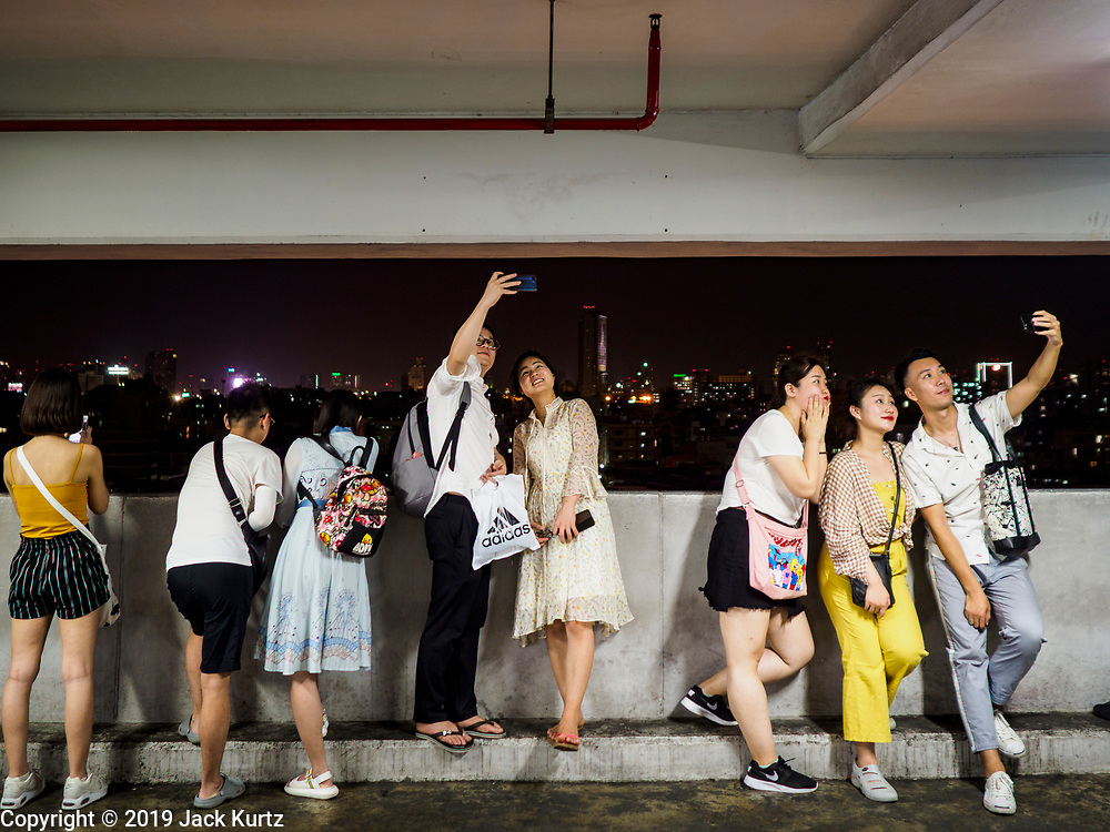 05 MARCH 2019 - BANGKOK, THAILAND:  Chinese tourists in a parking ramp take selfies with their smart phones of the Ratchada Night Market and Bangkok skyline. The Ratchada Night Market is the newest night market in Bangkok. It was originally a small night market popular with local people but now is tourism destination. Most nights the market is jammed with foreign tourists.     PHOTO BY JACK KURTZ