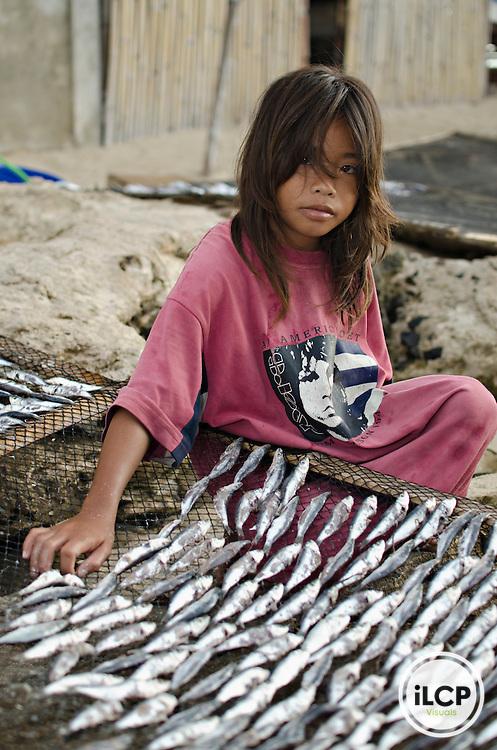 Girl laying out fish to dry in the sun; Bilangbilangan Island; Danajon Bank, Bohol, Philippines © Michael Ready / iLCP