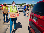 29 MAY 2020 - DES MOINES, IOWA: ELLA SUNDSPROM, a volunteer, carries a box of produce to a car during a produce distribution in a mall parking lot in Des Moines. The Des Moines Area Religious Council (DMARC) and Capitol City Fruit from Norwalk, IA, gave away 1,800 boxes of fresh produce with a mix of vegetables and fruit. The boxes contain enough produce to feed a family of four for a week. The produce was provided by the USDA Farmers to a Families food program. Because of the COVID-19 pandemic, the unemployment rate in Iowa hit 10.2% in May, the highest unemployment rate ever recorded in Iowa and food insecurity in Iowa is impacting communities throughout the state.          PHOTO BY JACK KURTZ