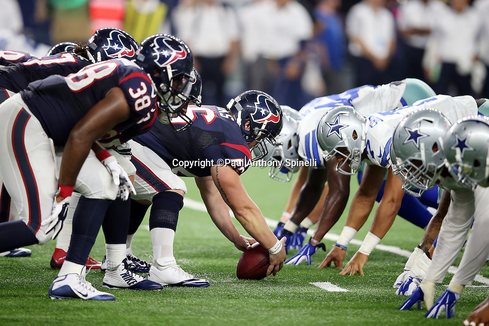 The Houston Texans offensive line gets set to snap the ball opposite the Dallas Cowboys defensive line during the 2015 NFL preseason football game against the Dallas Cowboys on Thursday, Sept. 3, 2015 in Arlington, Texas. The Cowboys won the game 21-14. (©Paul Anthony Spinelli)