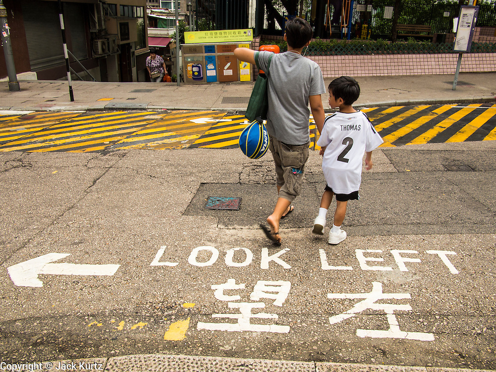 10 AUGUST 2013 - HONG KONG: A boy looks left while crossing a street in Hong Kong. Hong Kongs drives on the left hand side of the road and people from the Americas and Europe, where they drive on the right, have been hit crossing roads because they don't look the right direction. Hong Kong is one of the two Special Administrative Regions of the People's Republic of China, Macau is the other. It is situated on China's south coast and, enclosed by the Pearl River Delta and South China Sea, it is known for its skyline and deep natural harbour. Hong Kong is one of the most densely populated areas in the world, the  population is 93.6% ethnic Chinese and 6.4% from other groups. The Han Chinese majority originate mainly from the cities of Guangzhou and Taishan in the neighbouring Guangdong province.      PHOTO BY JACK KURTZ
