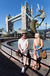 © Licensed to London News Pictures. 05/05/2018. London, UK. A couple sit in front of a fountain next to Tower Bridge during hot and sunny weather near the River Thames in London this morning. Photo credit: Vickie Flores/LNP