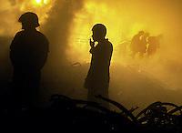 """Bomberos intentan apagar el fuego que se produjo en horas de la tarde en la fabrica de bicicletas """"Pipian"""" de la Habana, 4 de Marzo del 2002, la Habana, Cuba. Desde aproximadamente las 7 de la tarde se produjo este incendio y hasta el momento se desconocen las causas. (Photo/Cristobal Herrera)"""