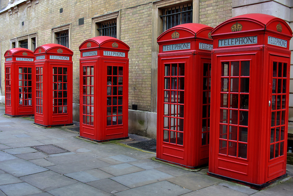 Five Red Telephone Booths in London, England<br /> The red telephone box evolved into an iconic symbol of the United Kingdom since Sir Giles Gilbert won a 1924 design competition. That earliest cast iron model was called Kiosk No. 2 or K2.  The Tudor Crown feature was added in 1926. Five additional models were introduced before production of the public phone booth stopped in the mid-1980&rsquo;s. Only about 11,000 of the total 314,000 telephone boxes remain in service. This row of K6s bearing the St Edward&rsquo;s Crown are on Broad Street. Their primary purpose today is as a photo opportunity using &ndash; what else? - a mobile phone.