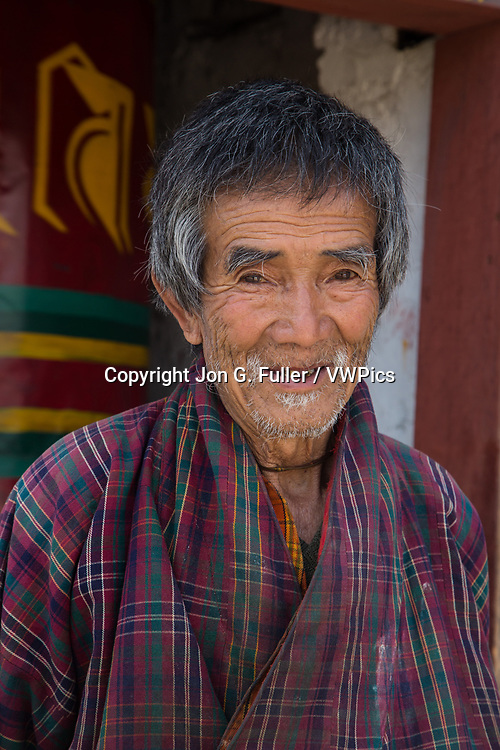 An old man in the traditional gho robe in Punakha, Bhutan.