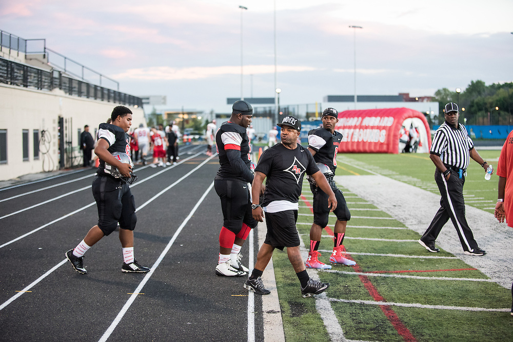 Al Raby head coach D'Angelo Dereef leads his team onto the field at Lane Tech Stadium for a game against Hubbard on September 10, 2015.