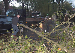 Motorists remove a branch from a main road in Central London, England  after a storm swept across Southern England disrupting transport in. London, United Kingdom. Monday, 28th October 2013. Picture by Max Nash / i-Images