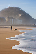 Woman and her dog walking on Zurriola beach in San Sebastian (Spain)